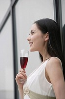Young woman with wineglass standing by glass wall