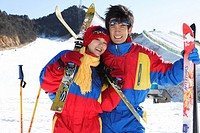 Portrait of young couple holding skis, smiling