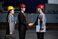 Businessmen shaking hands by businesswomen