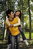 Young man giving woman piggyback ride, smiling
