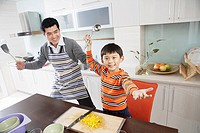 Portrait of father and son standing in domestic kitchen