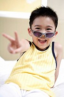 Boy wearing sunglasses and sitting on bed, smiling