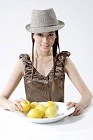 Portrait of a young woman with mangoes and hat