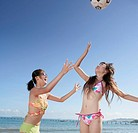 Two young women playing volleyball on beach