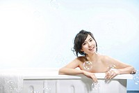Half-naked young woman sitting in a bathtub with water bubbles flying around