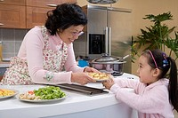 Grandmother handing dish to granddaughter in kitchen