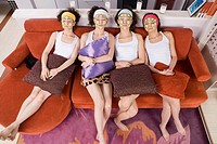 four fashionable women painting facial mask