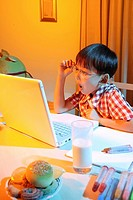 Boy sitting by laptop, making face