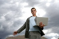 Man standing in desert, holding a laptop