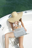 Young woman in hat using laptop on boat