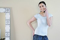 Young woman standing, smiling with a cell phone (thumbnail)