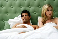 Young couple ignoring each other in bed