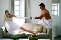 Young man pulling sheet of nude woman