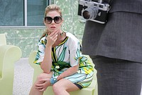 Fashionable woman sitting outdoors with photographer in foreground