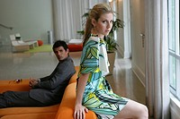 Fashionable woman sitting in hotel lobby with man watching