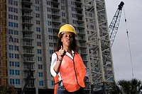 Portrait of a female architect gesturing in front of a building under construction