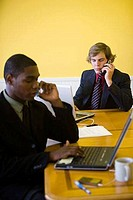 Businessmen in full suit using mobile phone and laptop in an office
