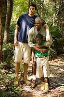 Mature man with his son and friend smiling at forest