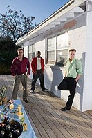 Portrait of friends standing on wooden deck by house