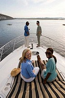 Portrait of smiling friends relaxing on the deck of a boat