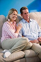 Cheerful mid adult couple sitting on a sofa