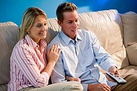 Cheerful mid adult couple with remote control sitting on a sofa