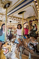 Portrait of cheerful teenage girls sitting in a carousel