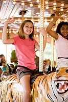 Portrait of cheerful teenage girls sitting on a carousel and waving hands