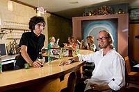 Portrait of mature man sitting by bar counter with family members around