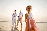 Girl standing on the beach with parents in the background