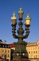 A lamp post with blue sky and buildings in the background