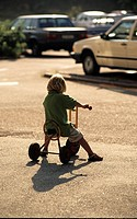 A child sitting on the toy bicycle and cars in the background