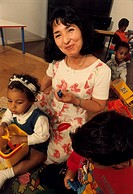 A teacher smiling with children in playschool
