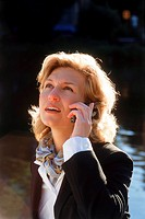 Close_up view of a business woman looking up while holding mobile phone