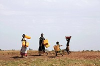 Refugees fetching water. Women and children carrying empty water containers to be filled. In undeveloped dry areas of the world, people have to walk l...