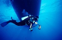 Scuba diver holding an underwater camera and swimming underwater