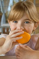Young girl eating orange