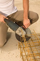 Low section view of a male construction worker cutting iron rods with a grinder