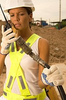 Close_up of a female construction worker talking on a walkie_talkie