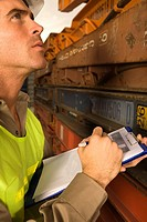 Close_up of a dock worker writing on a clipboard with a pen