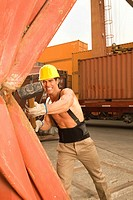 Mid adult man breaking a cargo container with a hammer