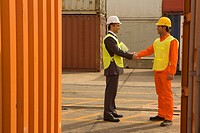 Side profile of a businessman shaking hands with a male dock worker