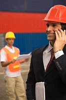 Close-up of a businessman talking on a mobile phone at a commercial dock (thumbnail)