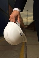 Close-up of a businessman's hand holding a hardhat (thumbnail)