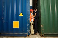 Side profile of a businessman and a female dock worker romancing between two cargo containers