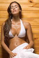 Young woman leaning against a wooden wall in a sauna