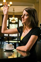 Close-up of a young woman sitting in a restaurant and waving her hand (thumbnail)