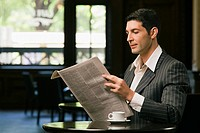Side profile of a young man reading a newspaper in a restaurant