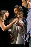 Close_up of two men and a woman toasting with champagne flutes in a restaurant