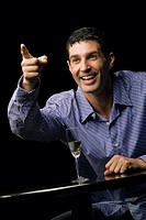 Close_up of a young man sitting in a restaurant and pointing with his finger